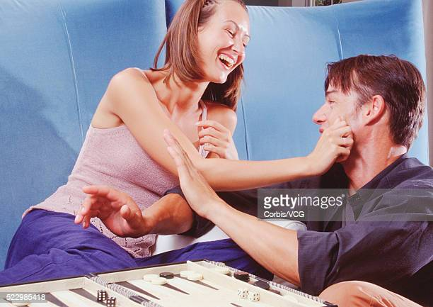 Playful Couple Playing Backgammon