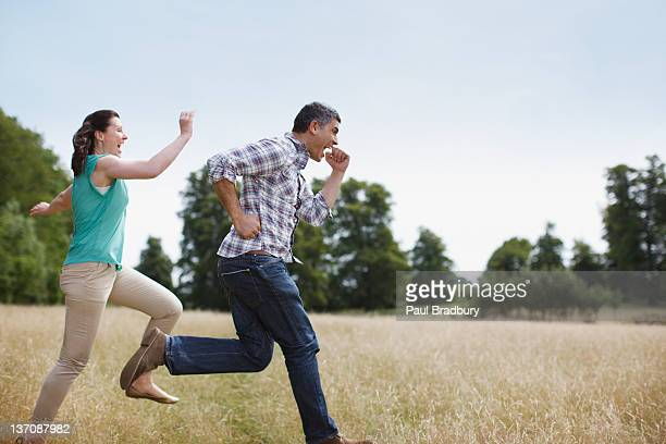 playful couple running in rural field - chasing stock pictures, royalty-free photos & images