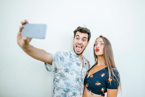 Playful couple taking a selfie with smartphone in front of white wall - gettyimageskorea