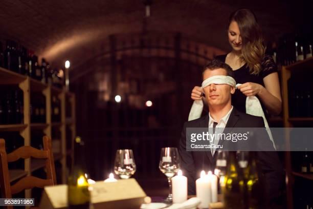 playful couple tasting wine blindfolded - donna bendata foto e immagini stock