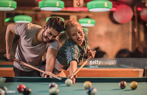 Playful couple trying to hit the same pool ball.