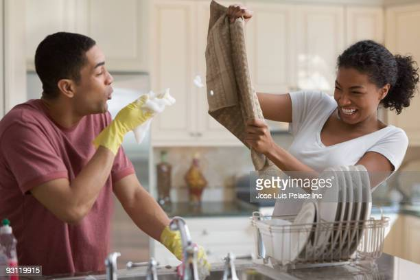 playful couple washing dishes - naughty america foto e immagini stock