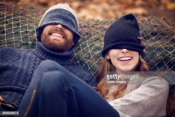 Playful couple wearing knit hat while leaning on Christmas tree in net