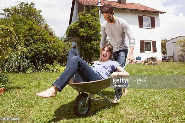Playful couple with wheelbarrow in garden
