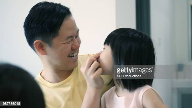 Playful dad pinches daughter's nose