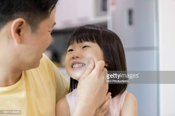 遊び心のあるお父さんが娘の頬をつまむ - 頬 ストックフォトと画像