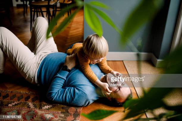playful daughter pinching cheerful father's cheeks on floor at home - spelen stockfoto's en -beelden