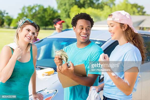 Playful diverse friends have fun during a car wash