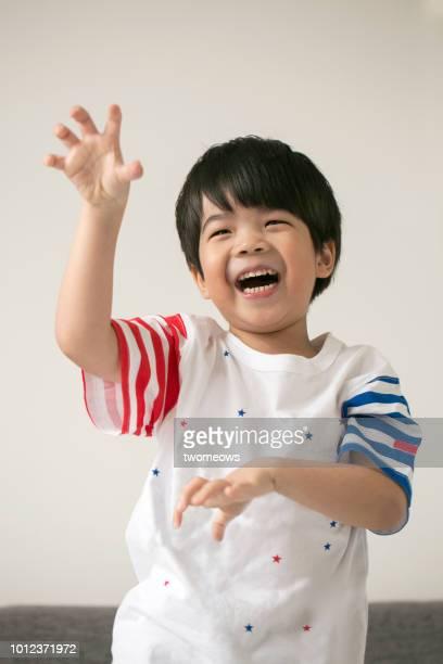 playful east asian young boy portrait. - actrice stockfoto's en -beelden