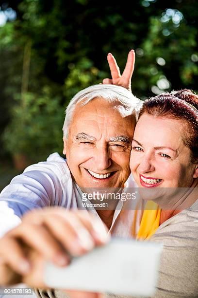 Playful elderly couple taking a selfie outdoors
