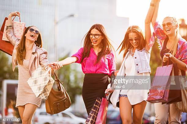 Verspielte elegante Frauen, die gemeinsam Spaß haben in Einkaufsmöglichkeiten.