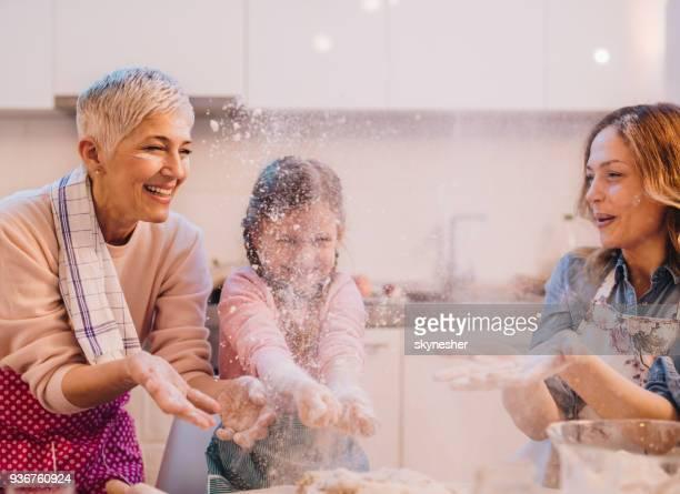 Juguetona familia divertirse con harina en la cocina.