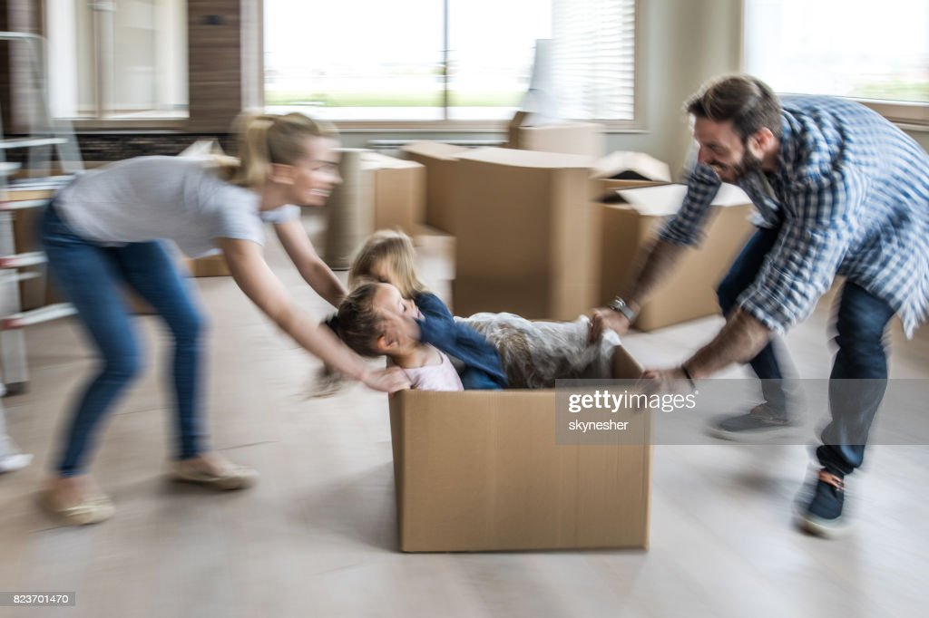 Playful family having fun after relocation in new home. Blurred motion. : Stock Photo