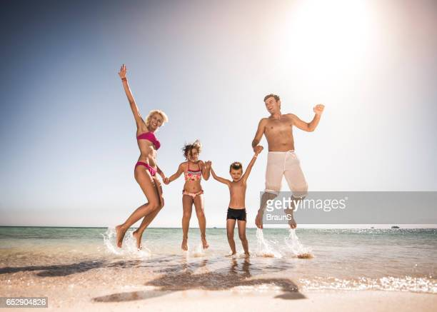 Playful family having fun while jumping on the beach.