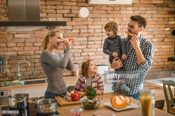 Spielerische Familie Spaß mit Karotten in der Küche.