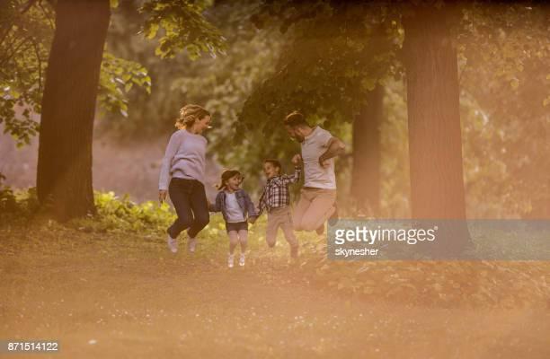 Família brincalhão pulando e se divertindo no parque.