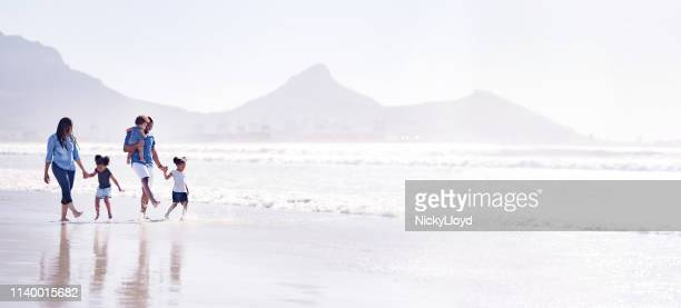 playful family on the beach - panoramic stock pictures, royalty-free photos & images