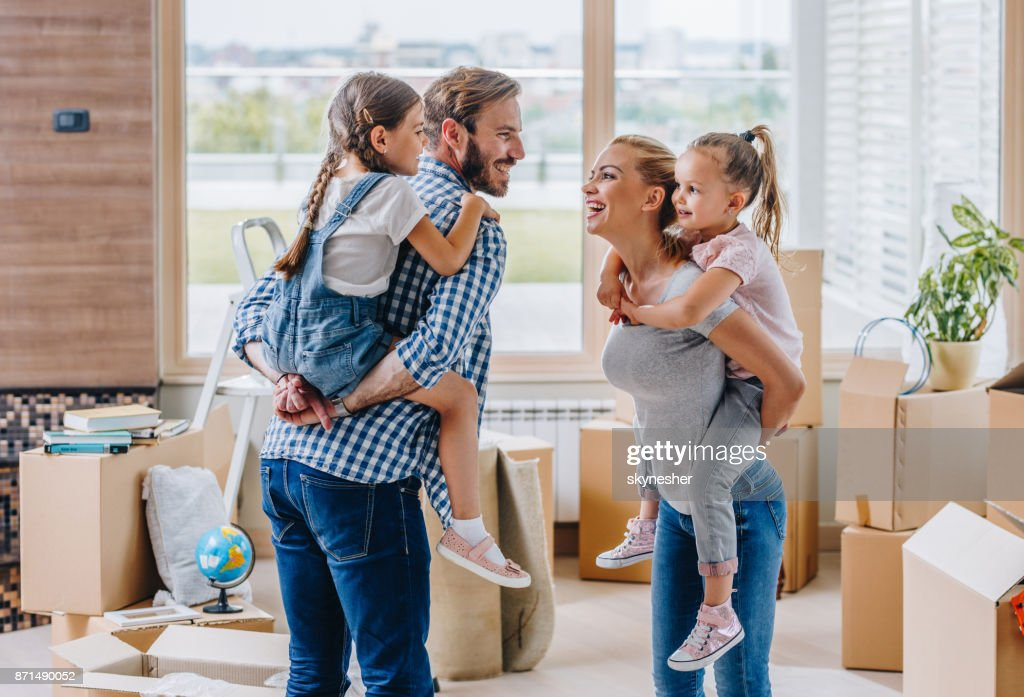 Playful family piggybacking while moving into new apartment. : Stock Photo