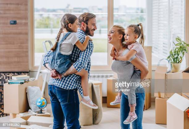 playful family piggybacking while moving into new apartment. - penthouse girls stock pictures, royalty-free photos & images
