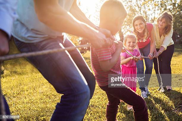 Playful family playing tug-of-war in the park.