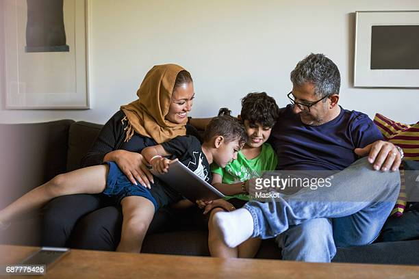 Playful family using smart phone while sitting on sofa at home
