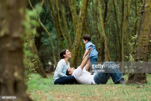 Spielerische Familie mit einem Kind sitzen auf dem Rasen