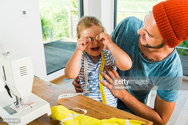 Playful father and daughter at home with sewing machine