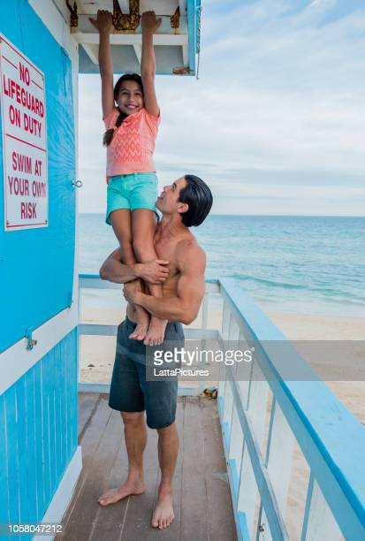 playful father and daughter having fun at lifeguard tower - of miami photos stock pictures, royalty-free photos & images