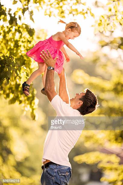 Playful father and daughter outdoors.