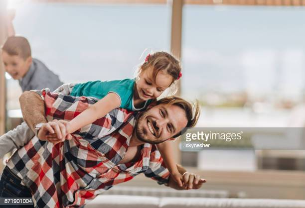 playful father and daughter piggybacking and having fun together. - penthouse girls stock pictures, royalty-free photos & images