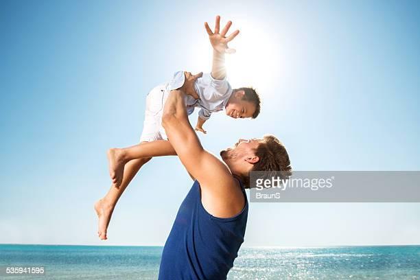 Juguetón Padre e hijo en la playa.