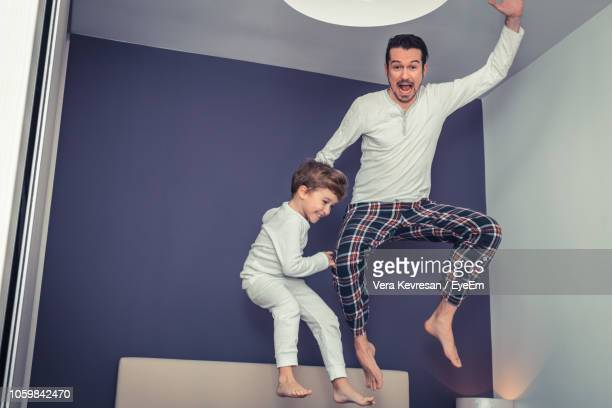 Playful Father And Son Jumping In Bedroom