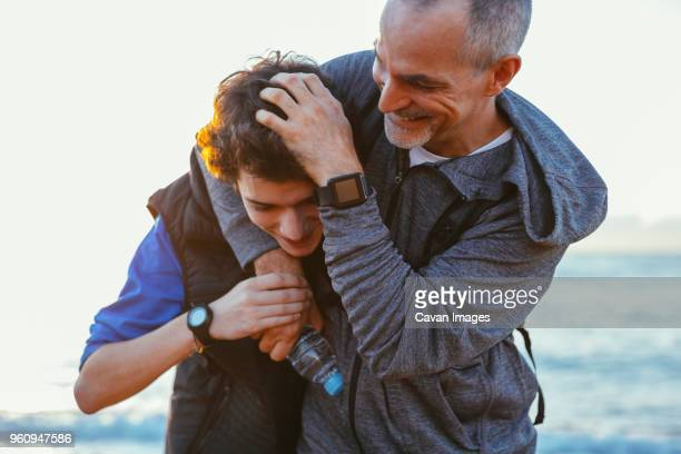 playful father and son playing while exercising at beach against sky - father stock pictures, royalty-free photos & images