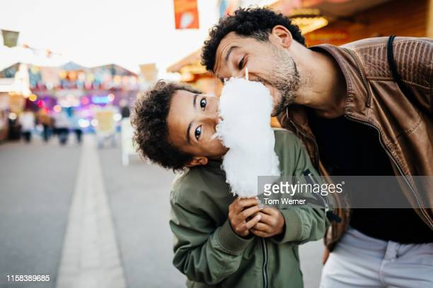 playful father and son sharing candy floss - teilen stock-fotos und bilder