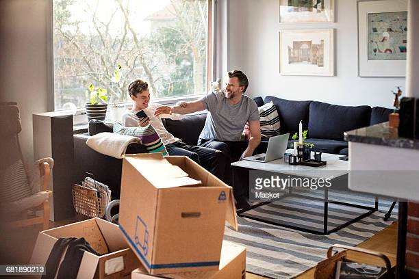 Playful father and son sitting on sofa at new home