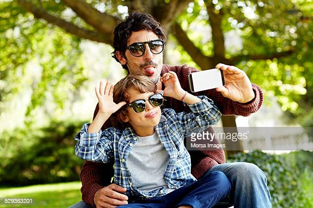 Playful father and son taking selfie in park