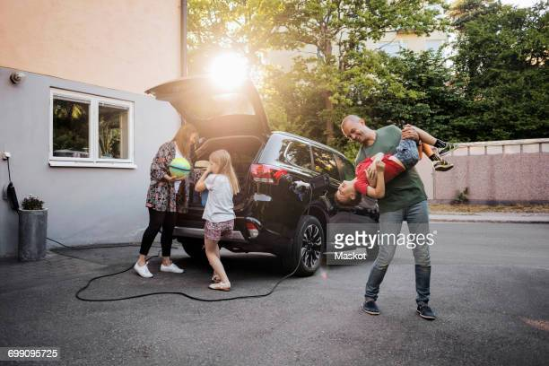Playful father and son with woman and girl standing by car in back yard