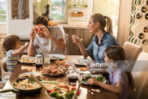 playful father entertaining his family during lunch at dining table. - almoço imagens e fotografias de stock