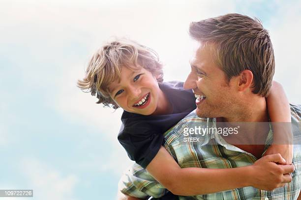 playful father giving his son piggy back ride against sky - piggyback stock pictures, royalty-free photos & images