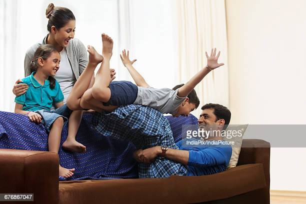 playful father lifting son overhead on sofa - indian subcontinent ethnicity stock pictures, royalty-free photos & images