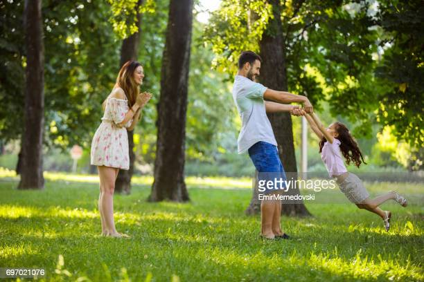 Playful father spinning his daughter in the park.