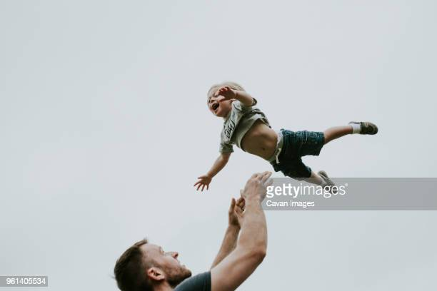 playful father throwing son in air against clear sky - lanciare foto e immagini stock