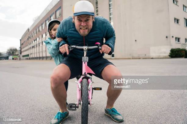 playful father with daughter on her bicycle - velo humour photos et images de collection