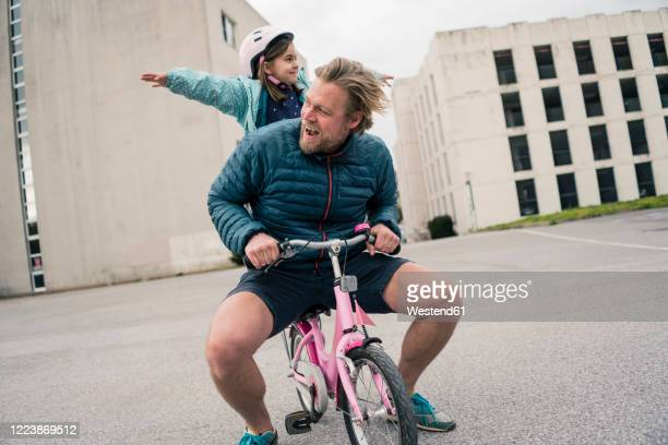 playful father with daughter on her bicycle - vater stock-fotos und bilder