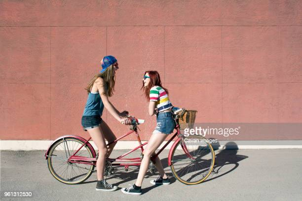 playful female friends sitting on tandem bicycle at sidewalk against wall - tandem bicycle stock pictures, royalty-free photos & images