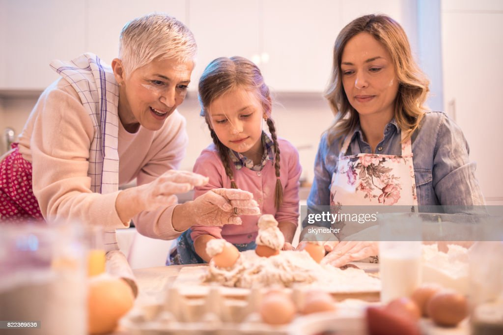 Playful female members of extended family having fun while baking in the kitchen. : Stock Photo