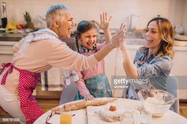 lúdicas mulheres membros da família se divertindo enquanto cozinhava na cozinha. - fazer um bolo - fotografias e filmes do acervo