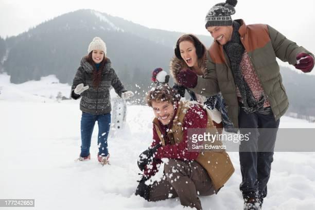Joyeux amis appréciant la bataille de boules de neige dans le champ