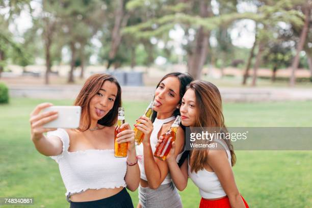 Playful friends in a park drinking beer and taking a selfie