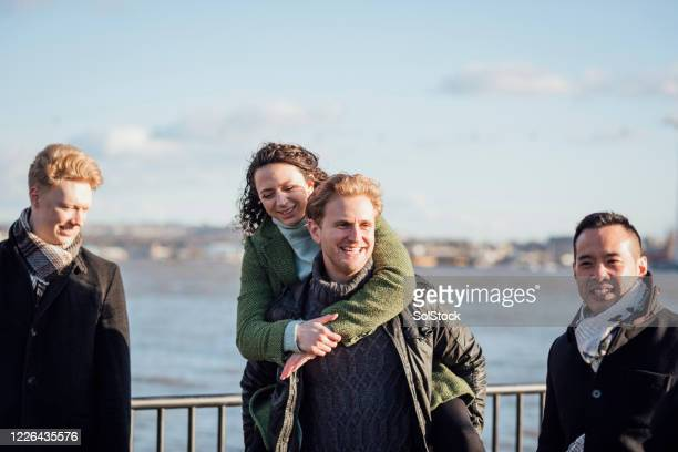 playful friends piggybacking - small group of people stock pictures, royalty-free photos & images
